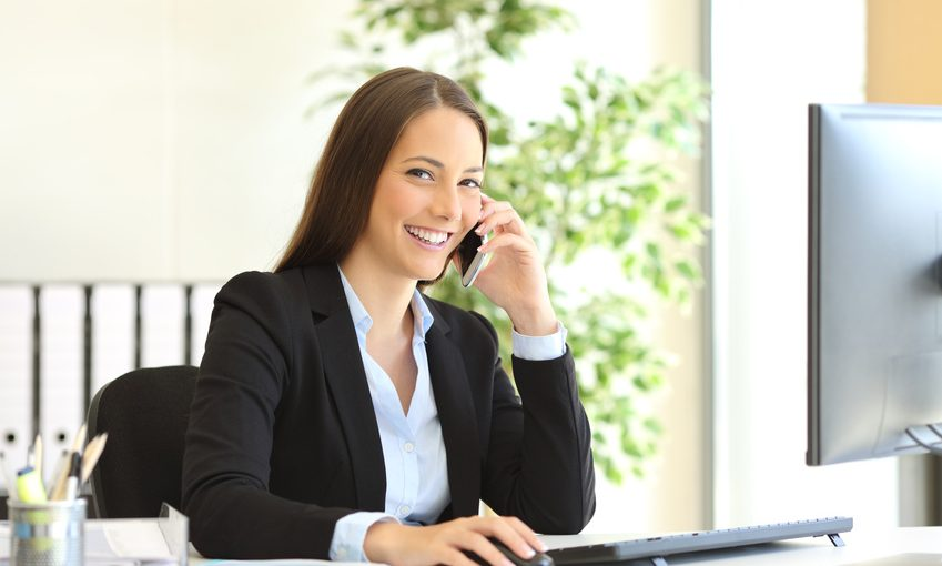 Portrait of a happy executive wearing suit calling customer service on the phone and looking at camera sitting on a desk in the office